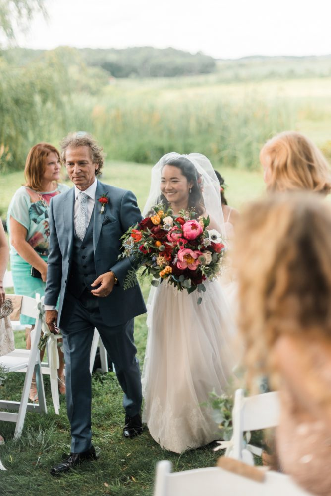 Bride Walking Down the Aisle: Vibrant Whimsical Wedding at Rustic Acres Farm from Dawn Derbyshire Photography featured on Burgh Brides
