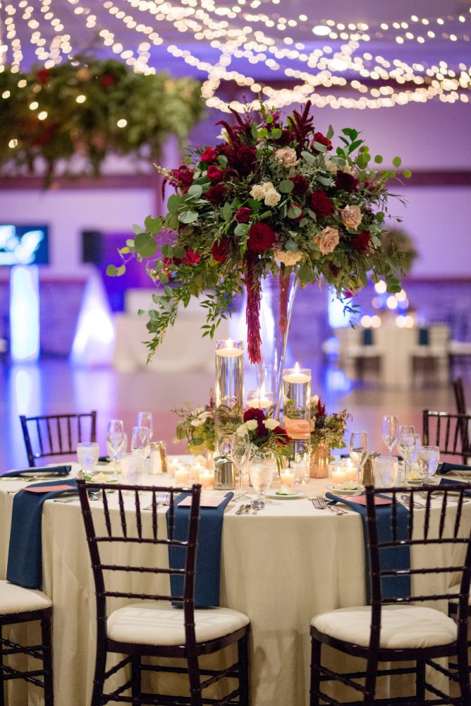 Tall Floral Centerpieces and Candles at Wedding Reception: Rustic Glam Wedding at Seven Springs from Simply Kacie Photography featured on Burgh Brides