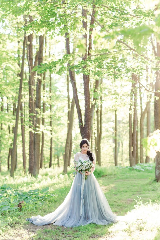 Bride in Dusty Blue Wedding Dress in Woods: Fresh Garden Party Wedding Inspiration from Jackson Signature Photography & Joy Filled Occasions featured on Burgh Brides