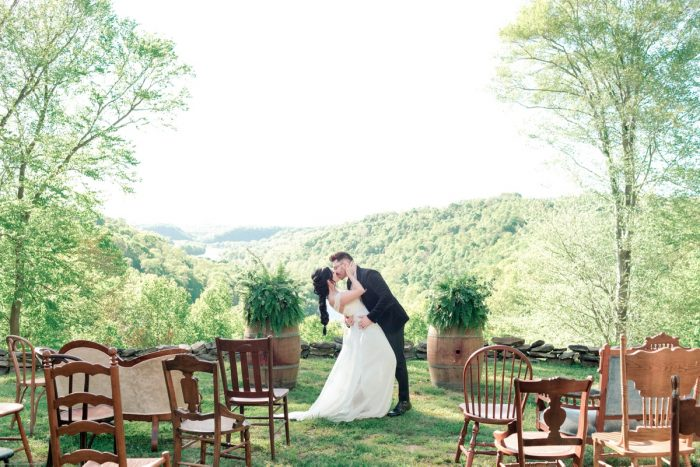 Bride and Groom Kissing at Ceremony Set Up with Wooden Chairs: Fresh Garden Party Wedding Inspiration from Jackson Signature Photography & Joy Filled Occasions featured on Burgh Brides