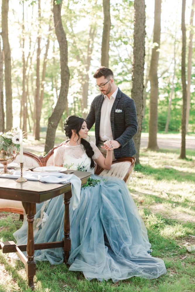 Bride in Dusty Blue Wedding Dress with Groom at Vintage Table in Woods: Fresh Garden Party Wedding Inspiration from Jackson Signature Photography & Joy Filled Occasions featured on Burgh Brides