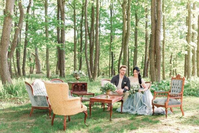 Bride in Dusty Blue Wedding Dress with Groom and Vintage Furniture in Woods: Fresh Garden Party Wedding Inspiration from Jackson Signature Photography & Joy Filled Occasions featured on Burgh Brides