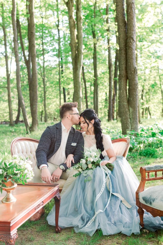 Bride in Dusty Blue Wedding Dress Kissing Groom in Woods: Fresh Garden Party Wedding Inspiration from Jackson Signature Photography & Joy Filled Occasions featured on Burgh Brides