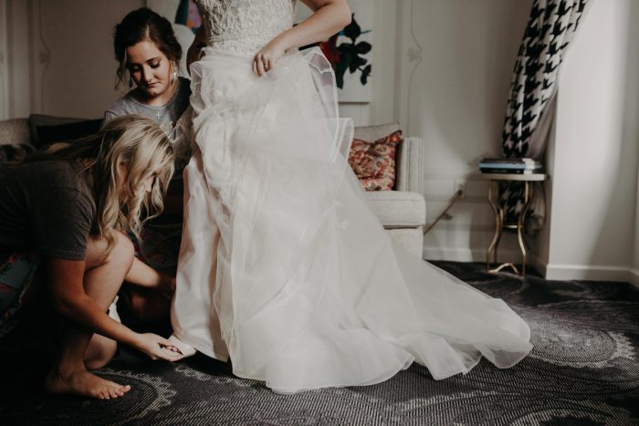 Bridesmaids Helping Bride into Wedding Shoes: Hip Pink & Blue Rooftop Wedding at Hotel Monaco from Rachel Rowland Photography featured on Burgh Brides