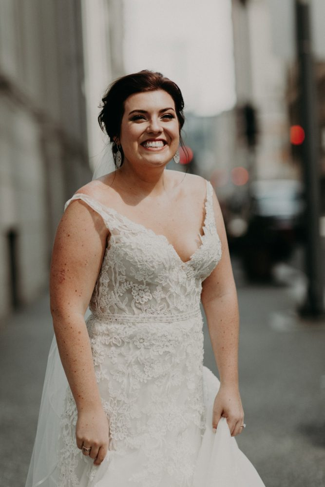 Bride Smiling in V Neck Wedding Dress with Straps: Hip Pink & Blue Rooftop Wedding at Hotel Monaco from Rachel Rowland Photography featured on Burgh Brides