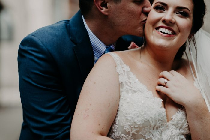 Groom Kissing Bride on Cheek: Hip Pink & Blue Rooftop Wedding at Hotel Monaco from Rachel Rowland Photography featured on Burgh Brides