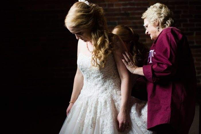 Mom and Bridesmaid Zipping Bride into Wedding Dress: Lush Blue & Burgundy Wedding at the Heinz History Center from Christina Montemurro Photography featured on Burgh Brides