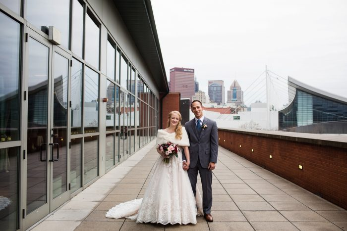 Bride and Groom on Balcony of Heinz History Center: Lush Blue & Burgundy Wedding at the Heinz History Center from Christina Montemurro Photography featured on Burgh Brides