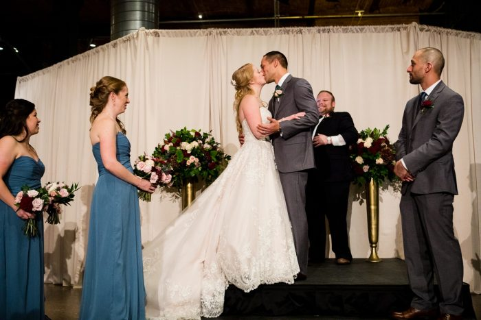 Bride and Groom First Kiss at Ceremony: Lush Blue & Burgundy Wedding at the Heinz History Center from Christina Montemurro Photography featured on Burgh Brides