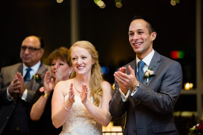 Bride and Groom Clapping at Reception: Lush Blue & Burgundy Wedding at the Heinz History Center from Christina Montemurro Photography featured on Burgh Brides