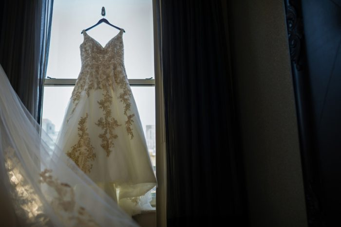Gold Brocade Wedding Dress Hanging on Window Frame: Parisian Inspired Wedding at the LeMont from Kristen Wynn Photography featured on Burgh Brides