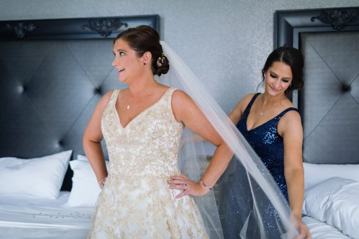 Bride in Gold Brocade Wedding Dress and Veil with Bridesmaid in Blue Sequin Bridesmaids Dress: Parisian Inspired Wedding at the LeMont from Kristen Wynn Photography featured on Burgh Brides