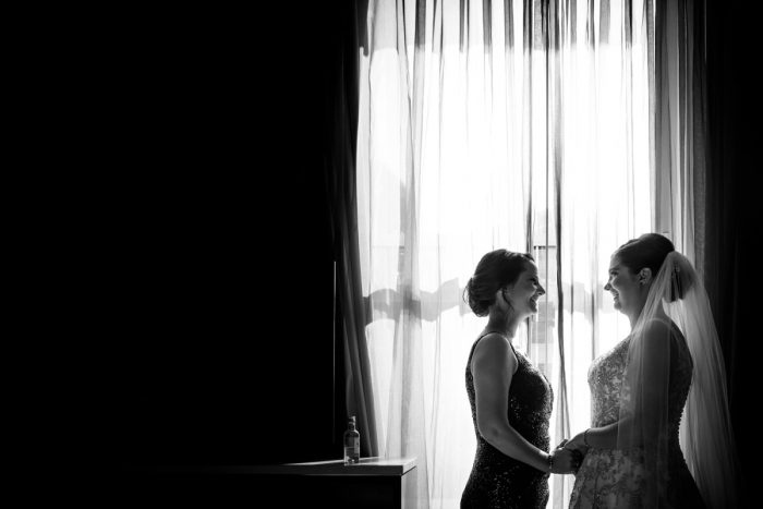 Bride and Bridesmaid Holding Hands on Wedding Day: Parisian Inspired Wedding at the LeMont from Kristen Wynn Photography featured on Burgh Brides