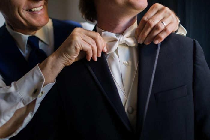 Groom in Ivory and Black Tuxedo Adjusting Tie: Parisian Inspired Wedding at the LeMont from Kristen Wynn Photography featured on Burgh Brides