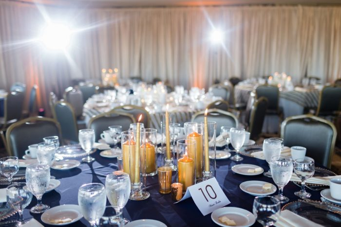 Navy blue linens with gold taper and pillar candles in glass hurricanes wedding centerpieces: Parisian Inspired Wedding at the LeMont from Kristen Wynn Photography featured on Burgh Brides