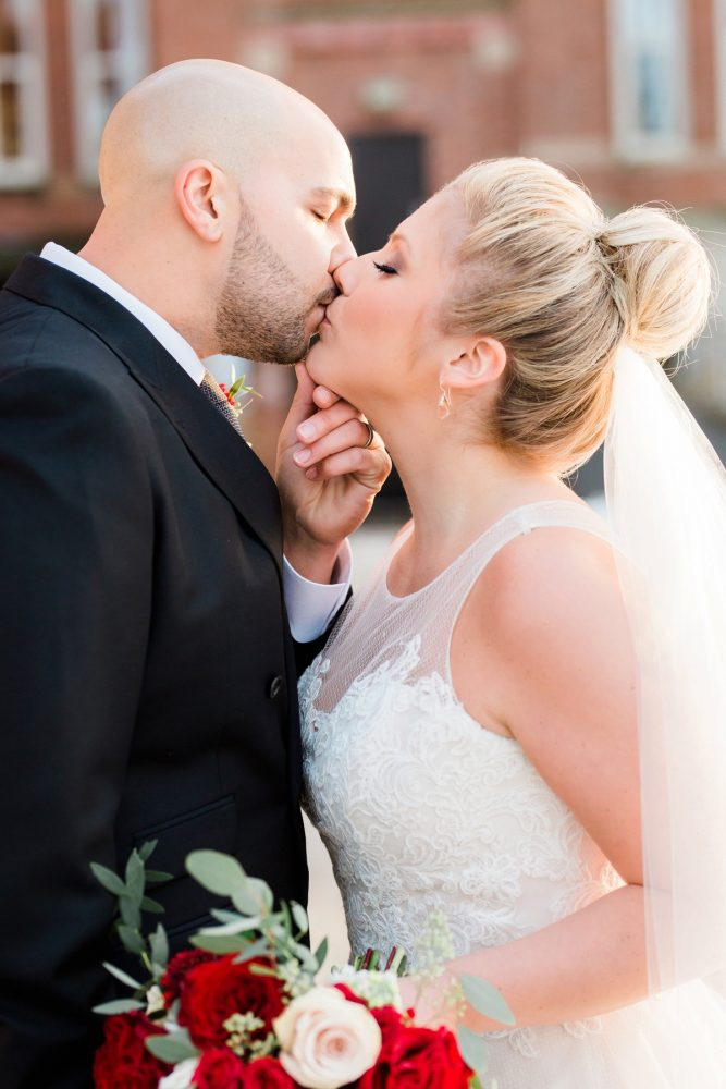 Groom Kissing Bride with Top Knot: Warm & Romantic Winter Wedding at Duquesne from Loren DeMarco Photography featured on Burgh Brides