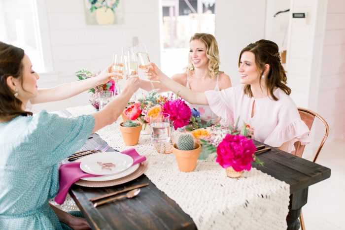Bridesmaids toasting at wooden table with pink flowers: Girly Cactus Themed Bridal Shower Inspiration from Olive & Rose Events and Abbie Tyler Photography featured on Burgh Brides