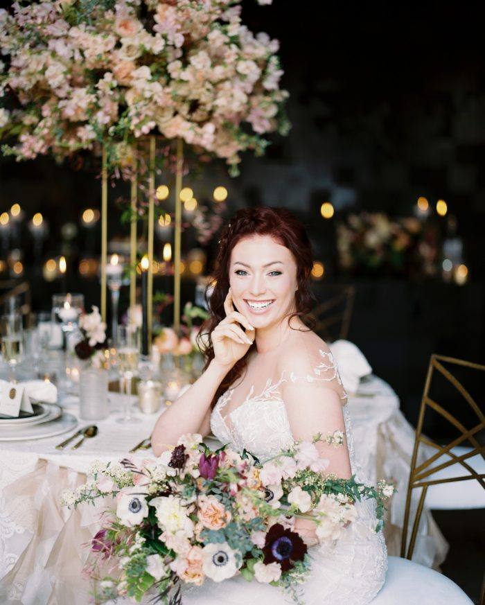 Bride Smiling at Table Holding Flowers: Romantic Edgy Wedding Inspiration from Poppy Events & Steven Dray Images featured on Burgh Brides