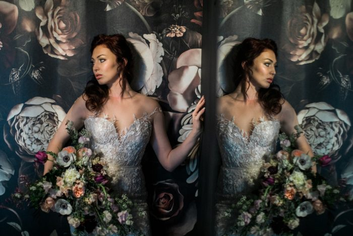 Bride in wedding dress holding bouquet against floral wallpaper: Romantic Edgy Wedding Inspiration from Poppy Events & Steven Dray Images featured on Burgh Brides
