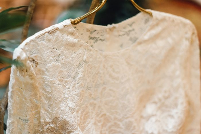 Lace Wedding Dress on Gold Hanger: Whimsical Greenhouse Wedding at Quality Gardens from Dawn Derbyshire Photography featured on Burgh Brides