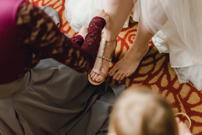Bridesmaid Helping Bride Put on Wedding Shoes: Whimsical Greenhouse Wedding at Quality Gardens from Dawn Derbyshire Photography featured on Burgh Brides