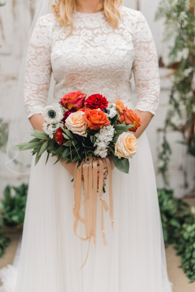 Bride in Long Sleeve Lace Wedding Dress with Red, Orange, and White Bouquet with Satin Ribbons: Whimsical Greenhouse Wedding at Quality Gardens from Dawn Derbyshire Photography featured on Burgh Brides