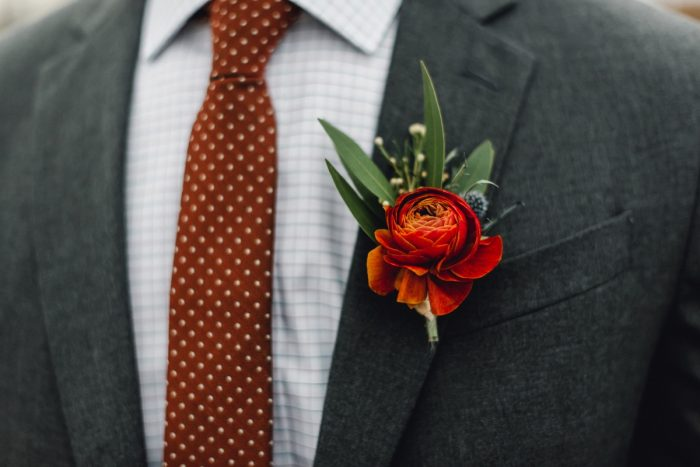 Groom Wearing Gray Suit, Burgundy Polka Dot Tie, and Red Ranunculus Boutonniere: Whimsical Greenhouse Wedding at Quality Gardens from Dawn Derbyshire Photography featured on Burgh Brides