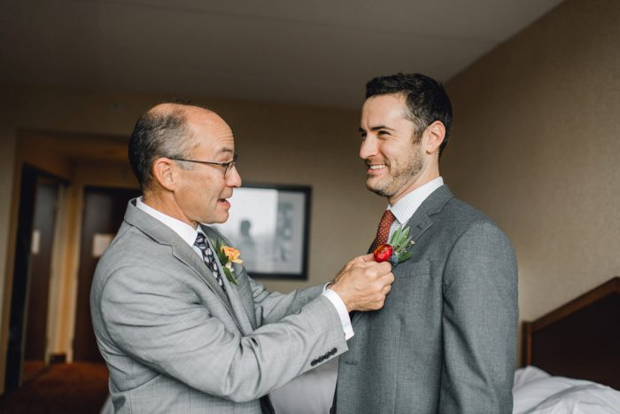 Dad Helping Groom with Tie: Whimsical Greenhouse Wedding at Quality Gardens from Dawn Derbyshire Photography featured on Burgh Brides