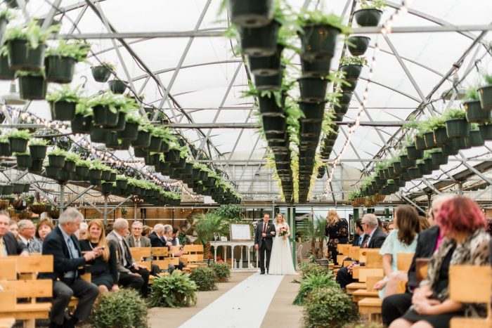 Bride Walking Down Aisle Wedding Ceremony in Greenhouse: Whimsical Greenhouse Wedding at Quality Gardens from Dawn Derbyshire Photography featured on Burgh Brides