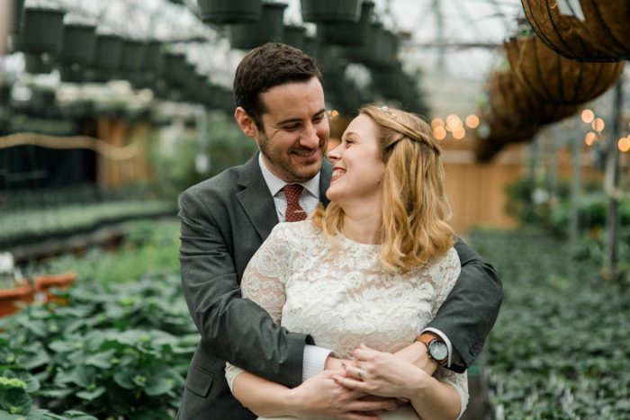 Groom Hugging Bride in Greenhouse: Whimsical Greenhouse Wedding at Quality Gardens from Dawn Derbyshire Photography featured on Burgh Brides