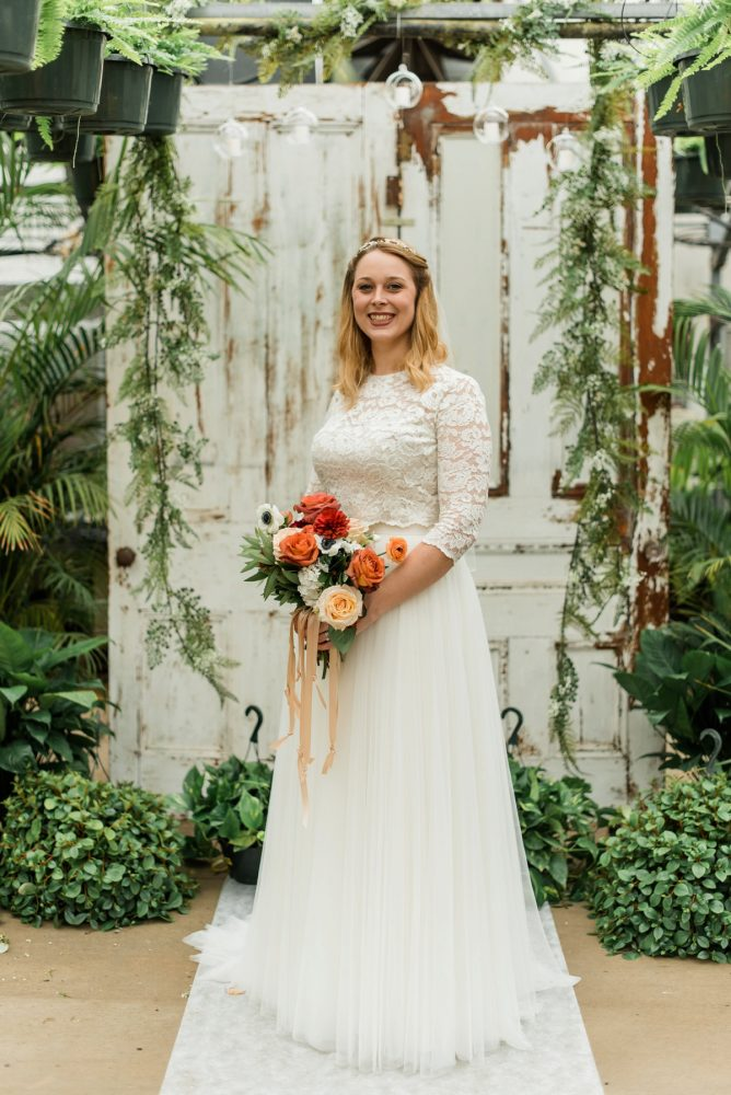 Bride in Lace Long Sleeve Wedding Dress with Red, Orange, Yellow, White Bouquet with Satin Ribbons: Whimsical Greenhouse Wedding at Quality Gardens from Dawn Derbyshire Photography featured on Burgh Brides
