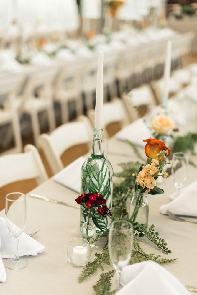 Wedding Centerpieces Taper Candles Glass Bottles Greenery Fresh Flowers: Whimsical Greenhouse Wedding at Quality Gardens from Dawn Derbyshire Photography featured on Burgh Brides