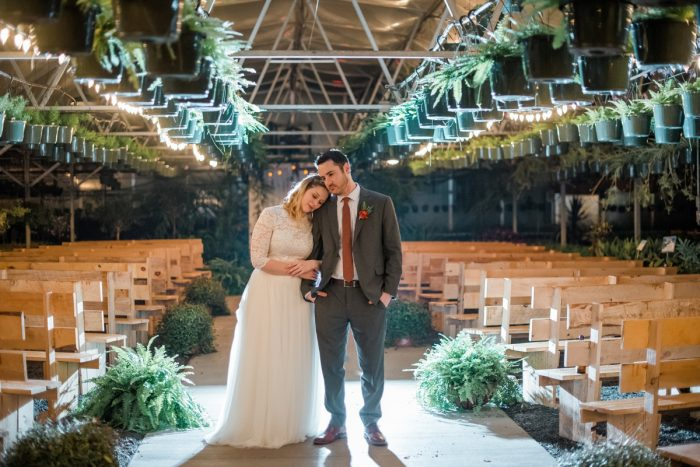 Bride Groom Hugging Greenhouse: Whimsical Greenhouse Wedding at Quality Gardens from Dawn Derbyshire Photography featured on Burgh Brides