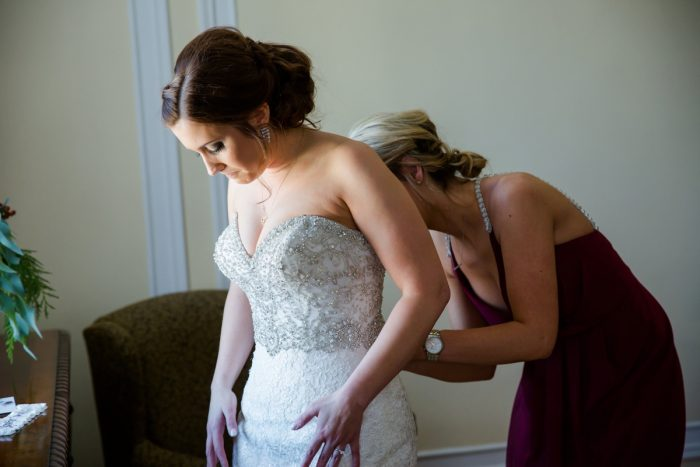 Bride Getting into Wedding Dress: Magical Christmas Wedding at the George Washington Hotel from Weddings by Alisa featured on Burgh Brides