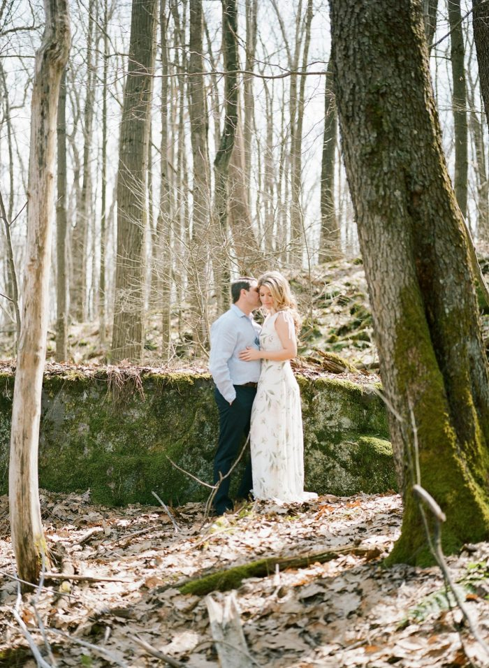 Woodsy engagement photo with leaves and trees. See more engagement photo ideas at burghbrides.com.