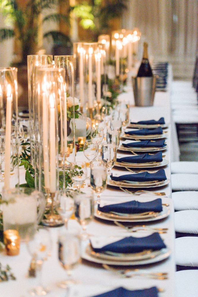 Navy blue napkins on gold chargers taper candles in glass cylinders: Amalfi Coast Inspired Wedding at The Pennsylvanian from Bumbleburgh Events & Leeann Marie Photography featured on Burgh Brides