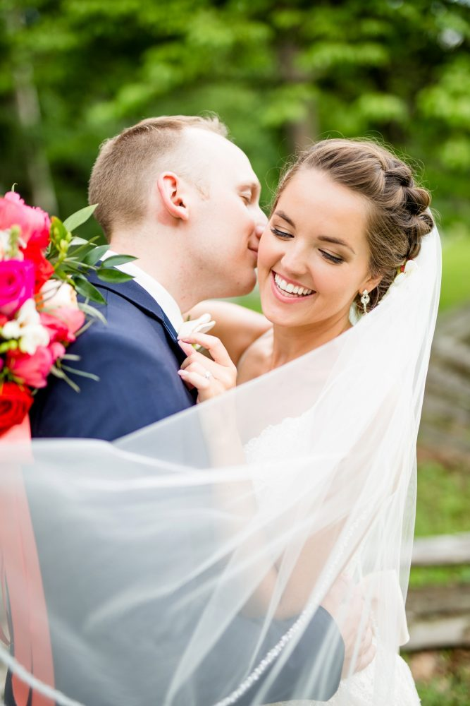 Groom kissing bride on cheek veil: Whimsical Teal Antonelli Event Center Wedding