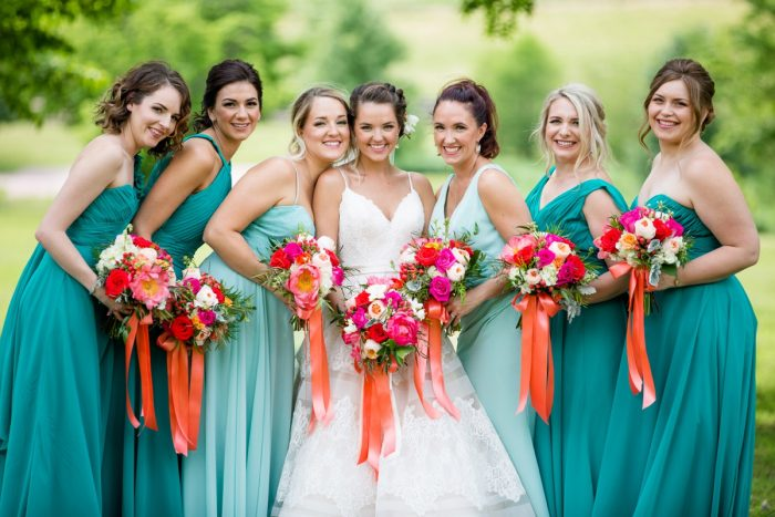 Mismatched teal bridesmaids dresses pink and orange bouquets satin ribbons: Whimsical Teal Antonelli Event Center Wedding