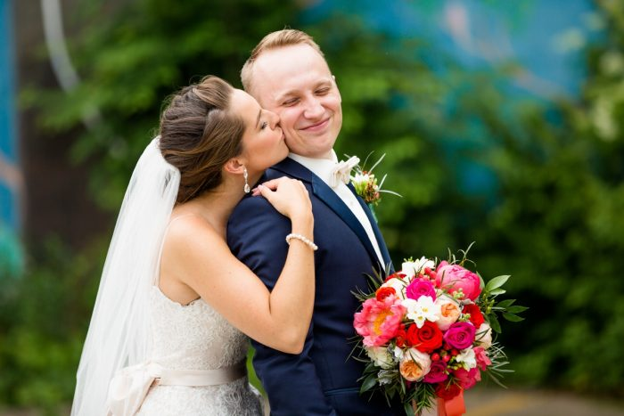 Bride kissing room on cheek hold pink and orange bouquet: Whimsical Teal Antonelli Event Center Wedding
