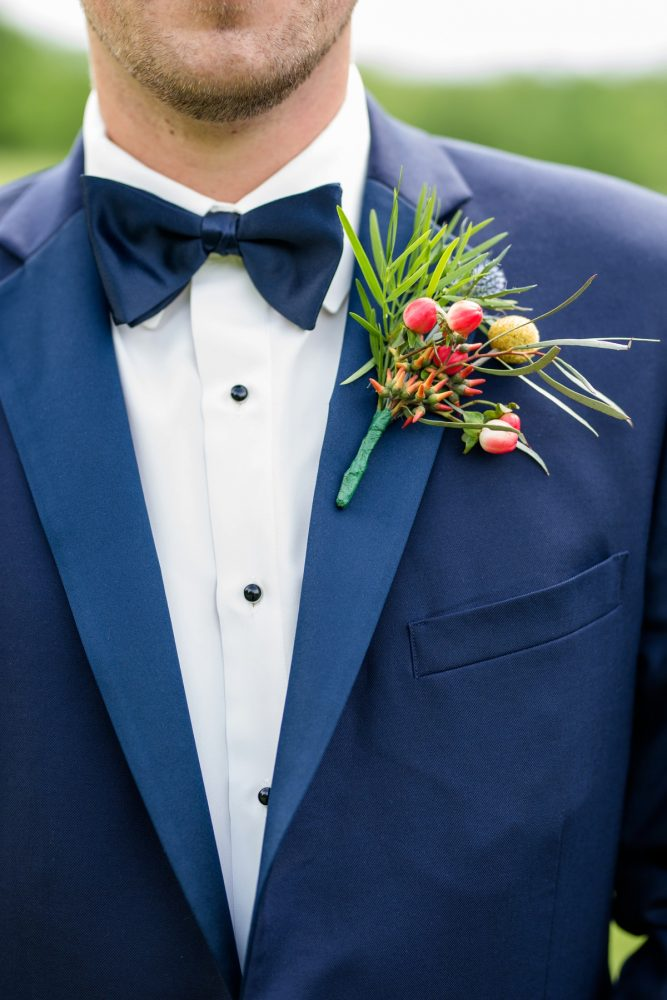 Groom navy blue tuxedo pink yellow boutonnière: Whimsical Teal Antonelli Event Center Wedding