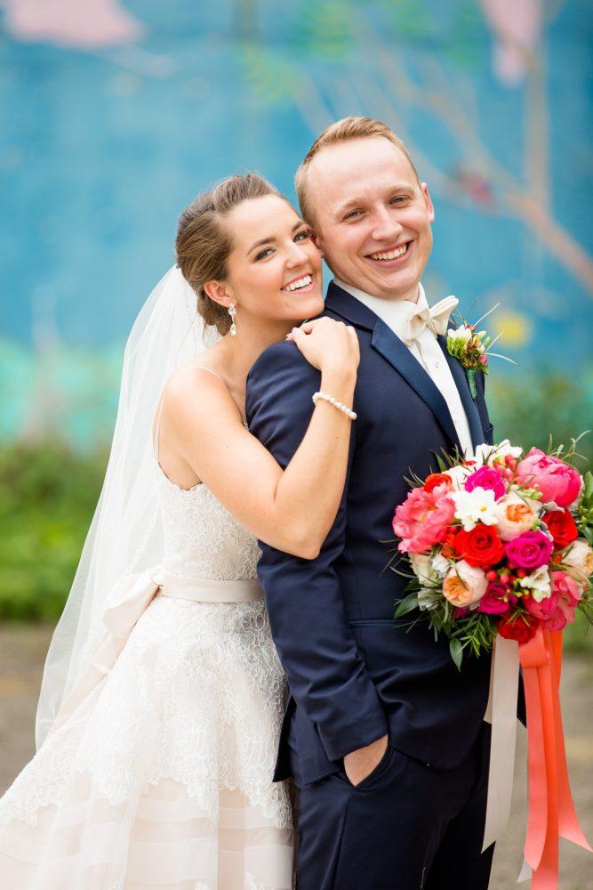 Bride hugging groom in navy blue tuxedo holding pink and orange bridal bouquet: Whimsical Teal Antonelli Event Center Wedding