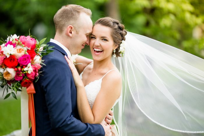 Groom hugging bride laughing veil: Whimsical Teal Antonelli Event Center Wedding