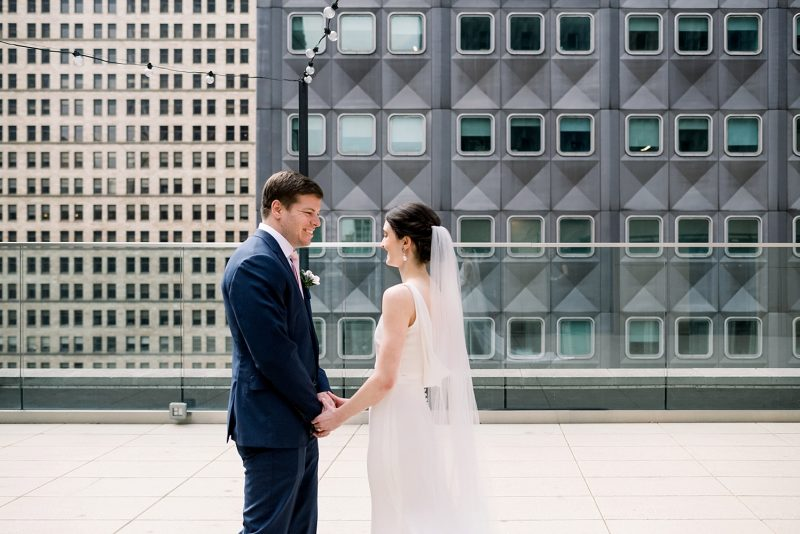 Bride and groom first look session on hotel rooftop
