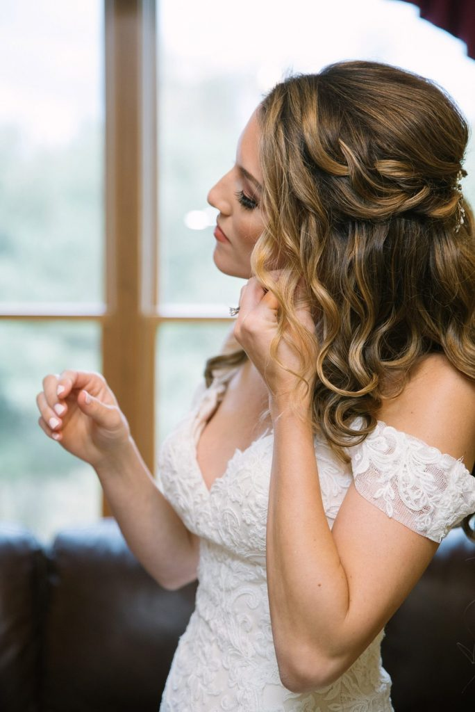 Bride putting on earrings in wedding dress on wedding day