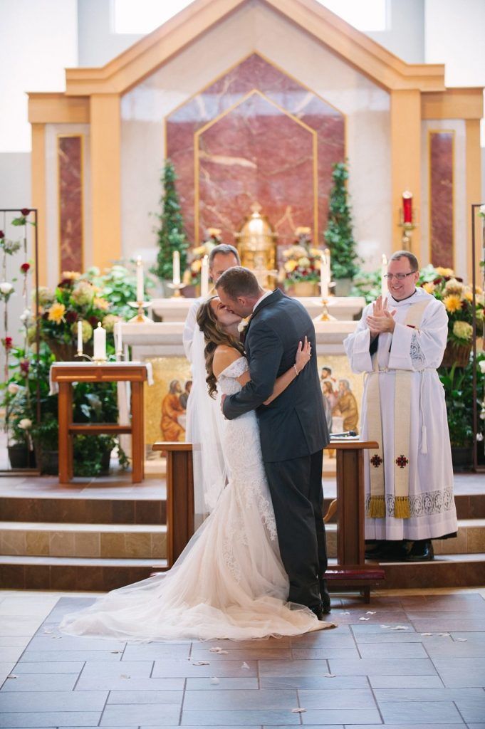Bride and groom first kiss at wedding ceremony