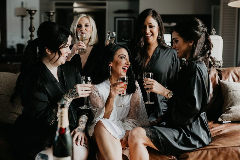 Brides with bridesmaids toasting with champagne