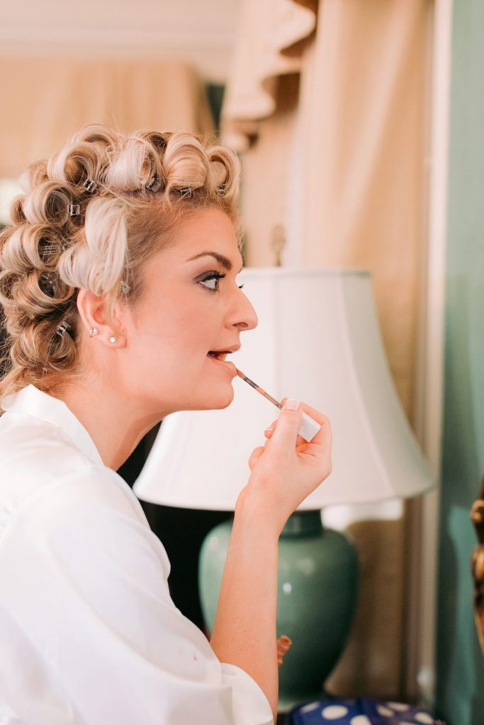 Bride putting on makeup in mirror